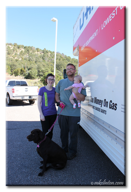 Young family with dog next to UHaul moving van