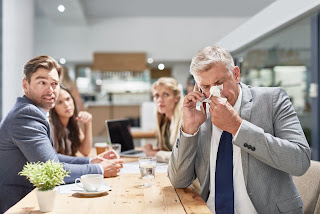 Coworkers wanting to avoid sick man blowing nose
