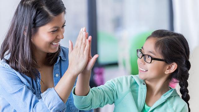 Professora elogiando aluna pelo bom comportamento