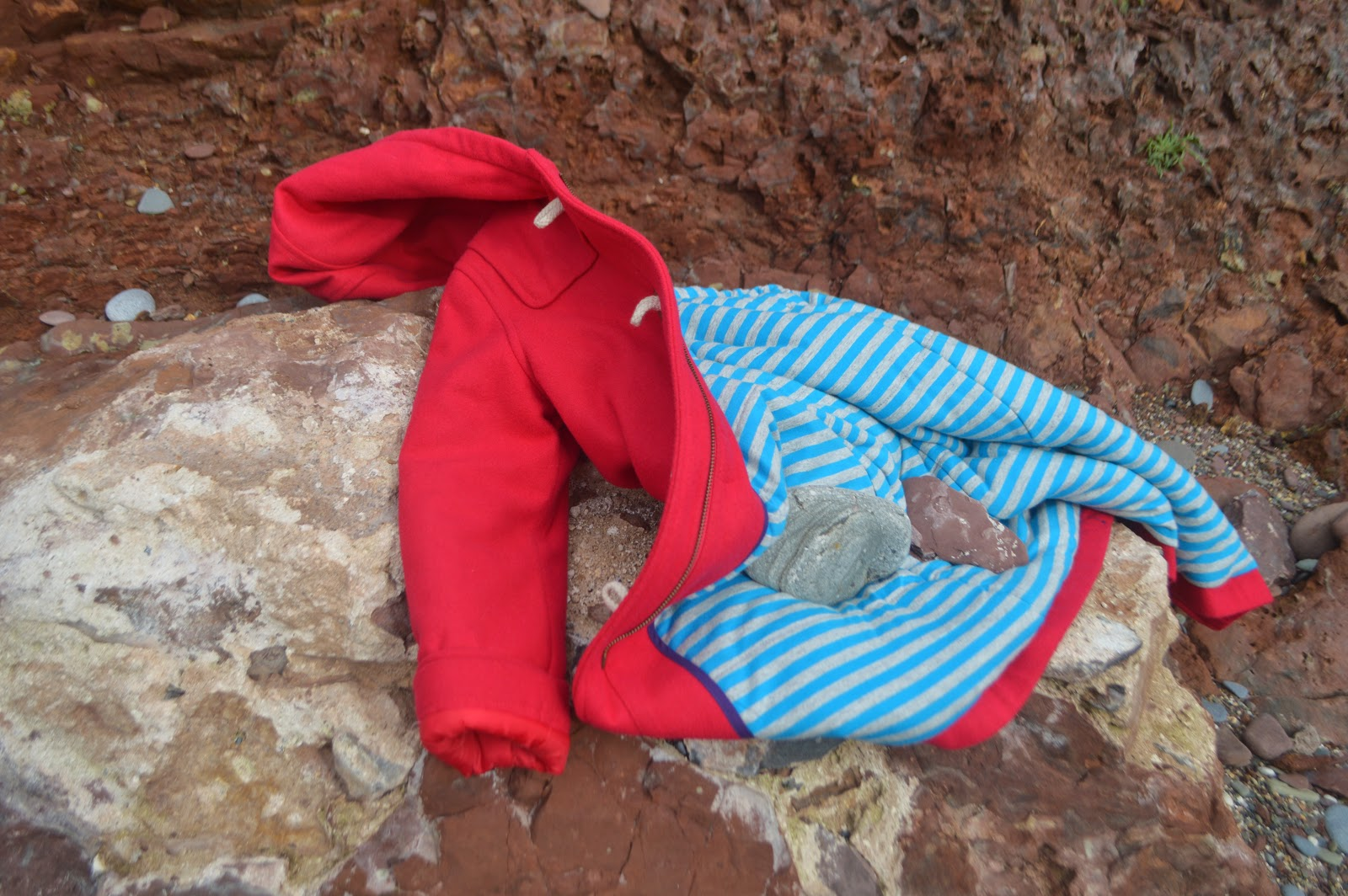 Red Boden Coat on Rocks at Manorbier Beach, Pembrokeshire, Wales