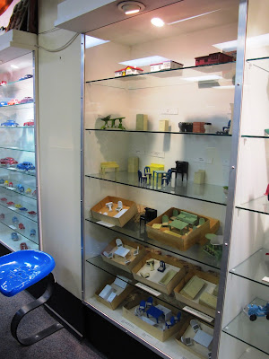 Glass display case containing shelves with various sets and pieces of metal dolls' house furniture displayed on them.