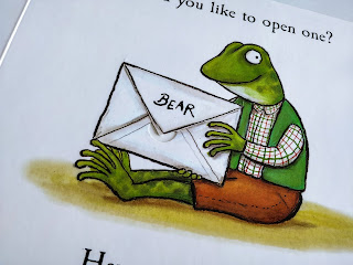 An up close photo of a frog wearing brown trousers, a  shirt with green and red check lines under a green vest jacket is holding a letter that reads Bear.