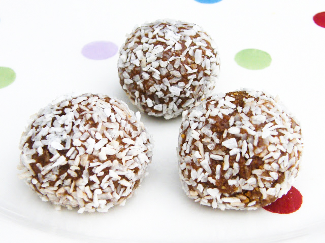 3 Scottish chocolate truffles rolled into coconut, on a spotty white plate