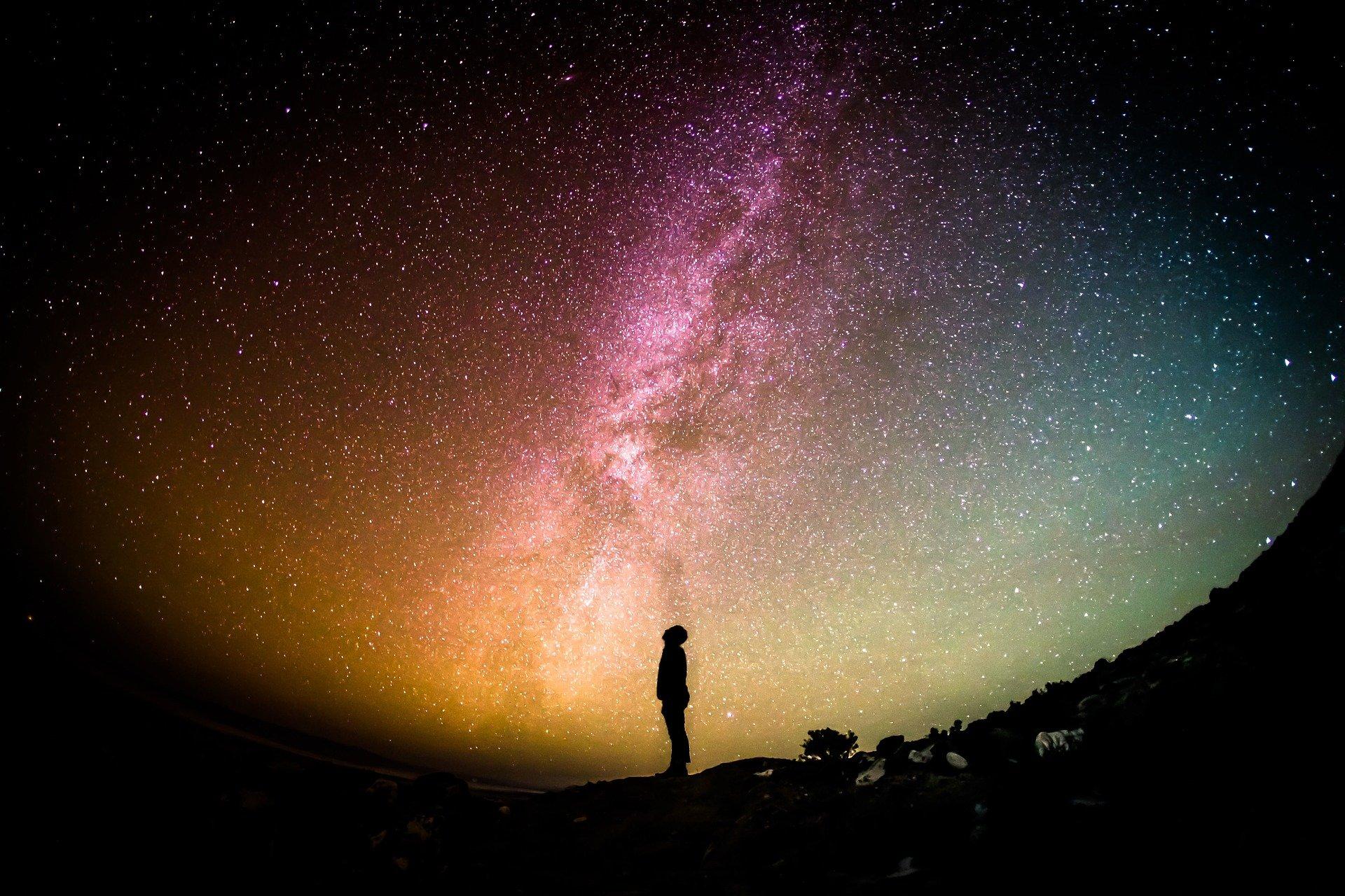 صورة رائعة للسماء ورجل ينظر اليها كأنما يحاول الوصول إليها
