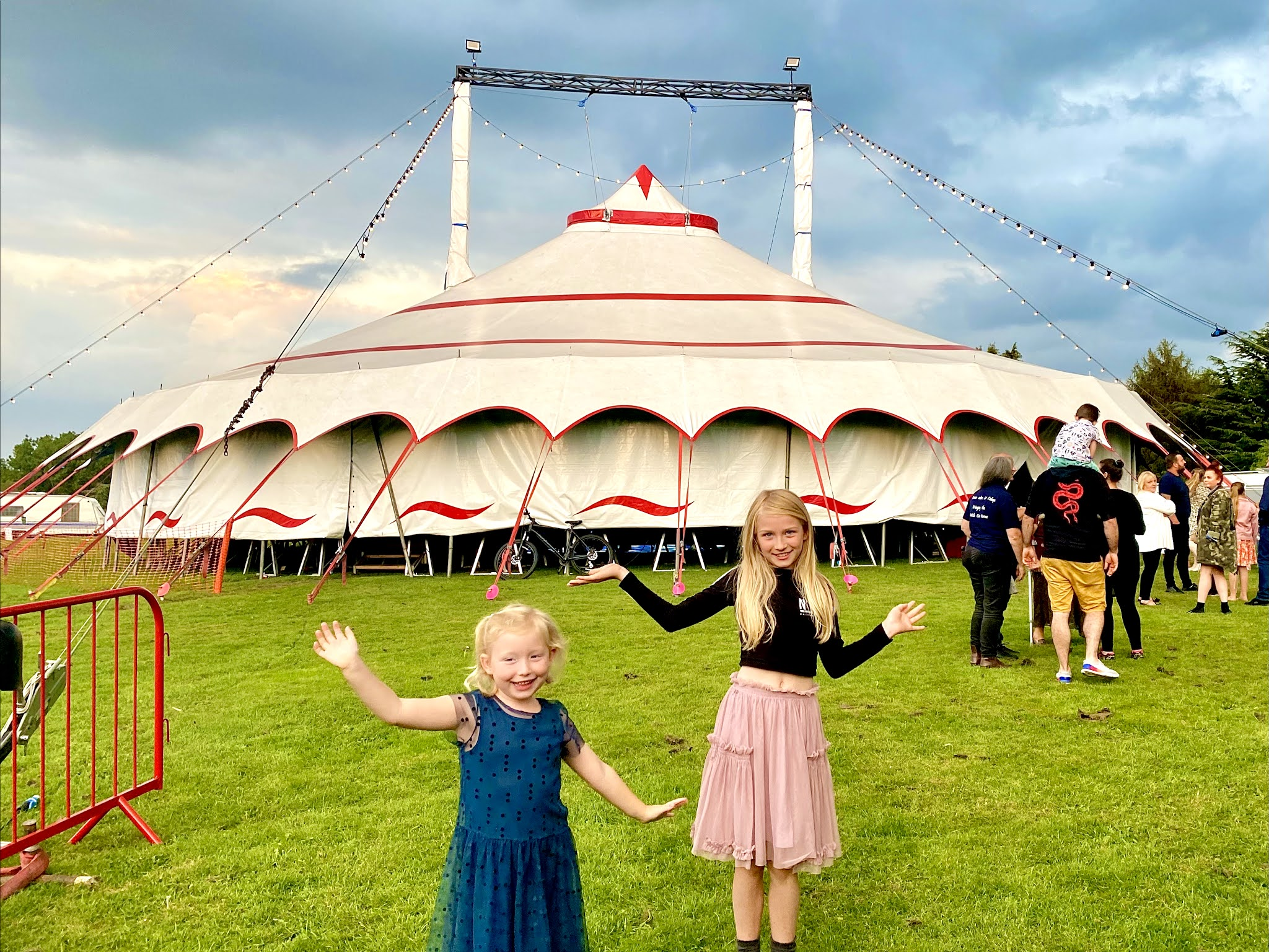 2 girls doing jazz hands outside the Circus Cortex tent having watched it as a review