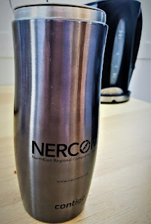"A tall 16oz stainless steel mug with ""NERCOMP"" on the side of it."