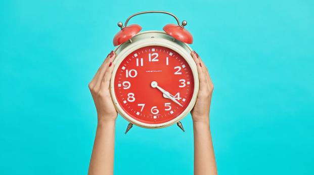A big alarm clock in someones hands
