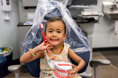 image of child sitting in dental chair holding fake teeth and toothbrush while smiling. Text:Colgate