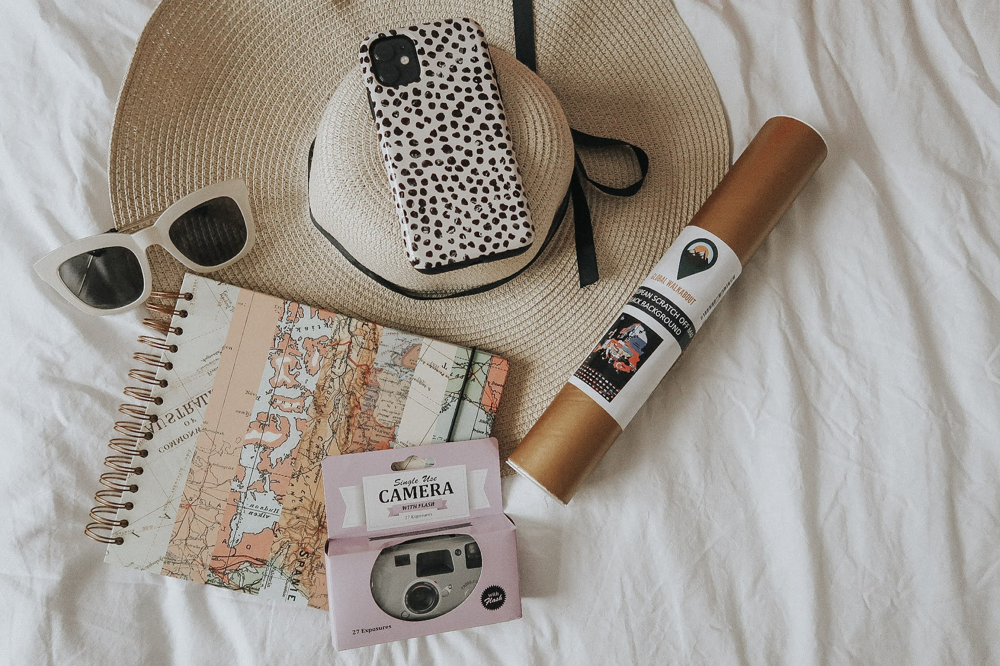 A purple disposable camera, white sunglasses, a gold rolled up map and scrapobook.