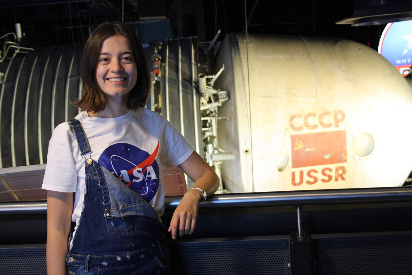Abbey, wearing a NASA t-shirt and dungarees, stands in front of a USSR space craft