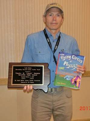 Charles Standen holding award and book titled Flying Circus of Physics.