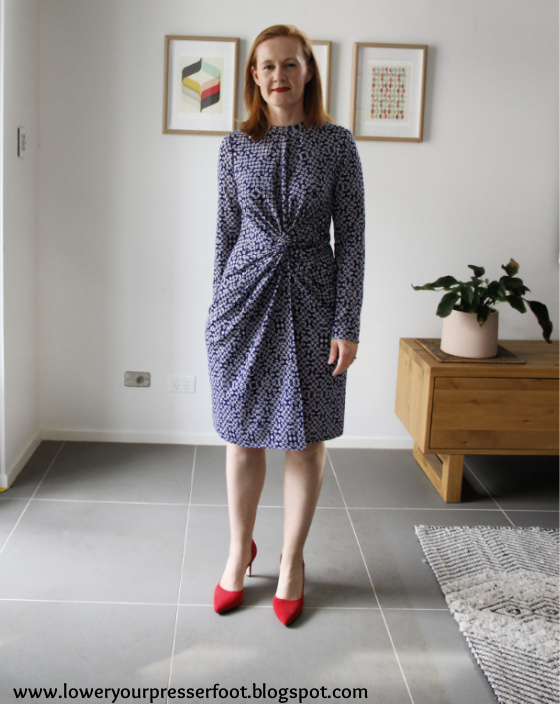 white lady posing in a blue dress with red shoes in a lounge room