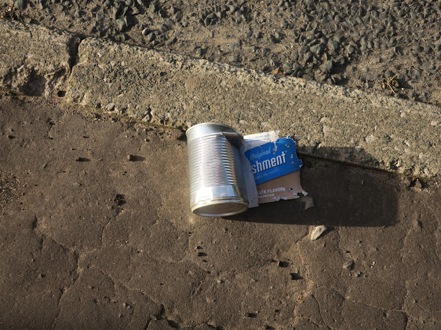 Abandoned chocolate nurishment tin on pavement in evening light.