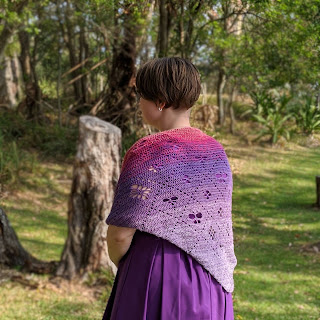 Sarah is standing in a grassy clearing surrounded by trees, she is wearing a purple and pink crochet shawl and purple dress. She is standing facing away from the camera at an angle looking to the left.