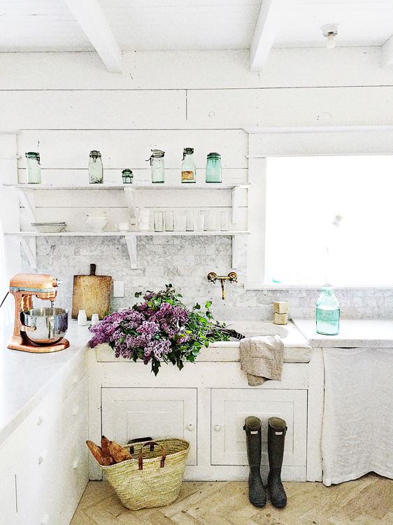 French farmhouse kitchen with white cabinets, carrara marble, and herringbone floors. Dreamy Whites.