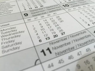 A close-up view of a calendar, showing the number of each month as well as its name in six languages, and the days of the month corresponding to days of the week with their English names. Each week is also sequentially numbered. The month of September is fully visible, while October and November are visible in part.