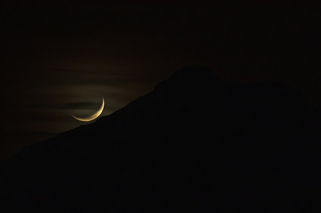 A crescent moon lies low over a dark mountain