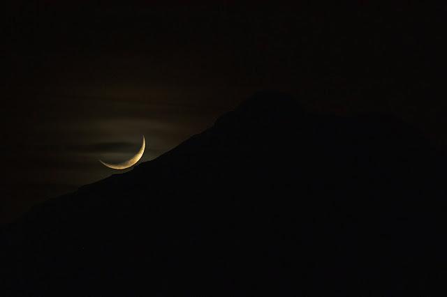 A crescent moon lies low over a dark mountain