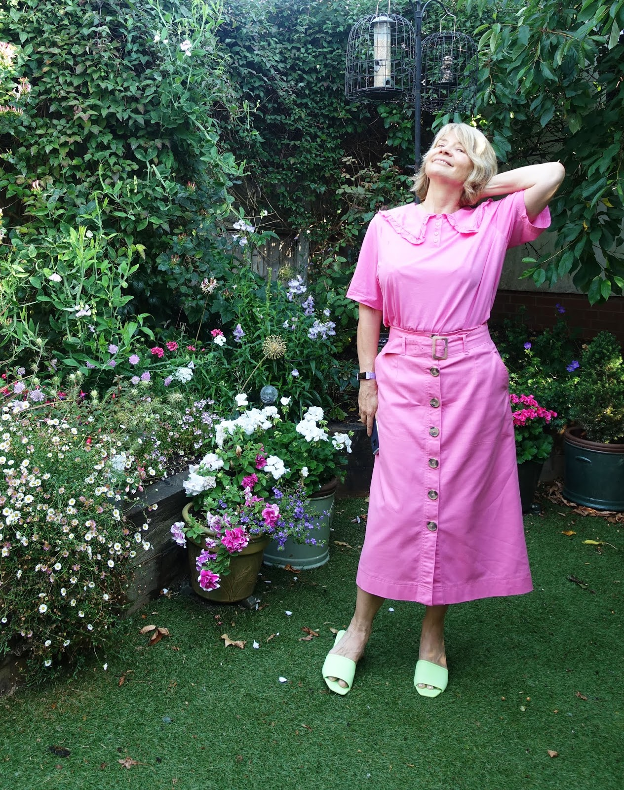 Over 50s blogger Gail Hanlon in pink top with statement collar and pink A line belted skirt with lime green mules