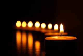 """Image is an illustration of lit candles with text that states: """"Disability Day of Mourning: remembering people with disabilities murdered by their families."""" Photo credit: Hyde Park Art"""
