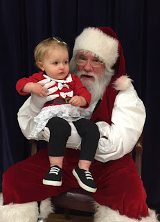 Santa holding a young baby in red shirt, bow in hair and black pants