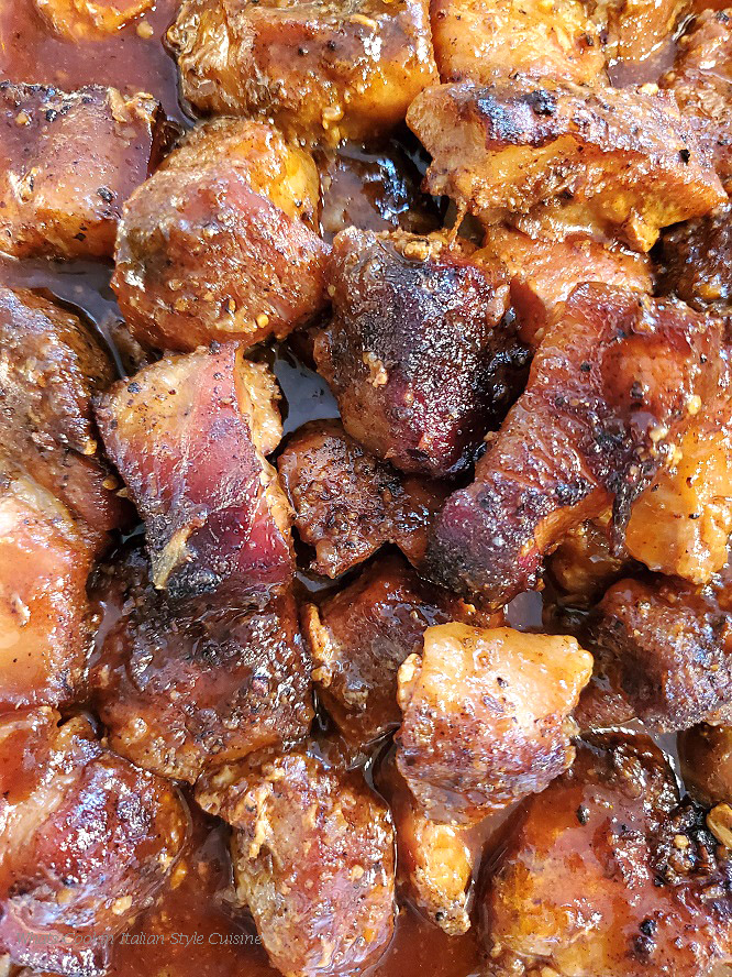 This is a pan of burnt ends in a butter honey sauce baked with an espresso barbecue rub on top