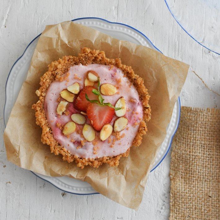 Pie de fresas con yogurt, la base se prepara con galletas de avena y se decora con almendras y fresas frescas