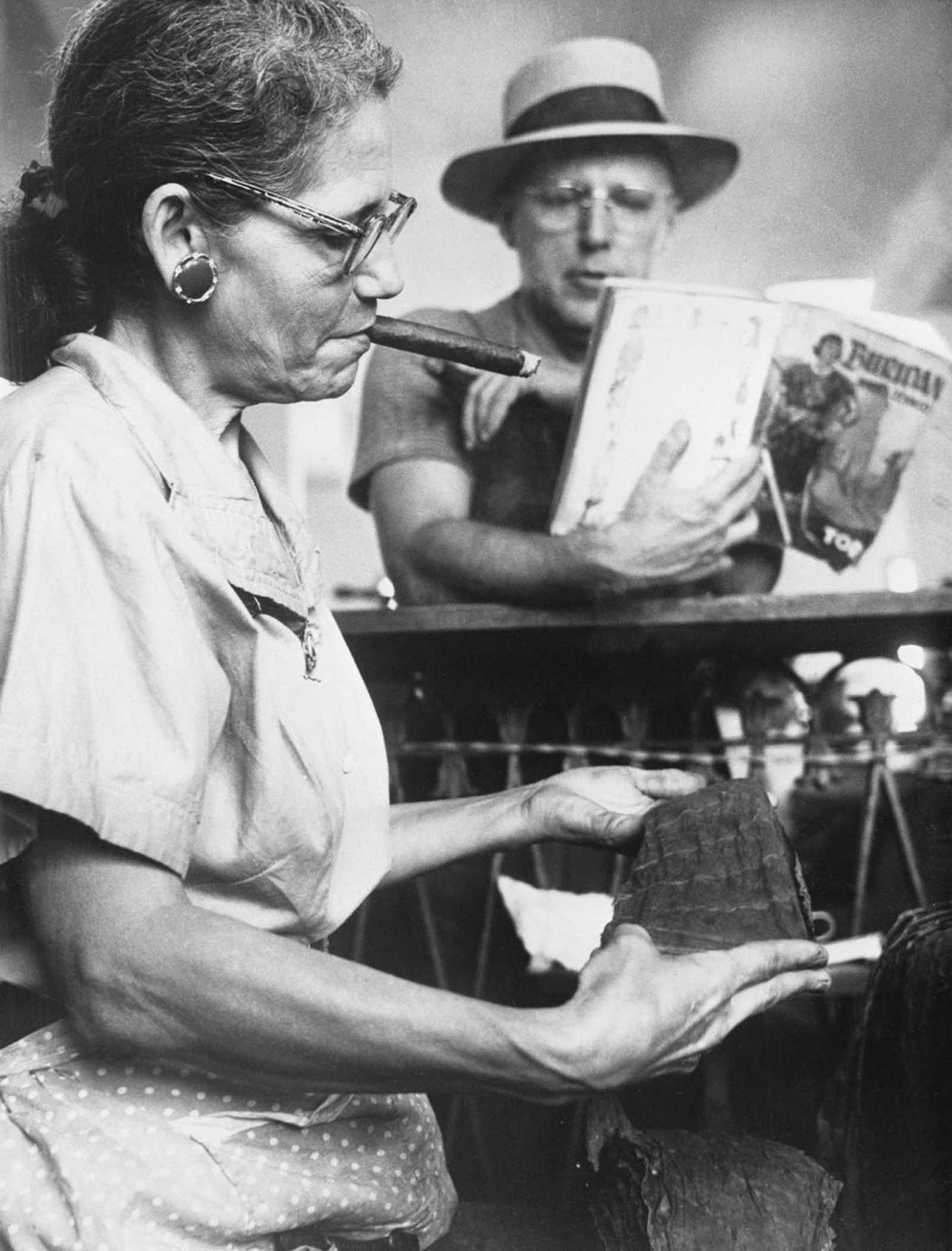 A lector reads a book to a worker in the Piedra Cigar factory in Maianao, Cuba. 1960.
