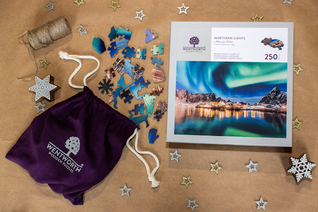 A 250 piece Wentworth Puzzles jigsaw of the Northern Lights pouring out of a fabric bag with some of the whimsy shapes visible