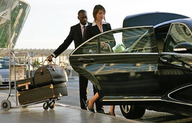 Mulher entrando no carro e homem colocando bagagens no porta malas