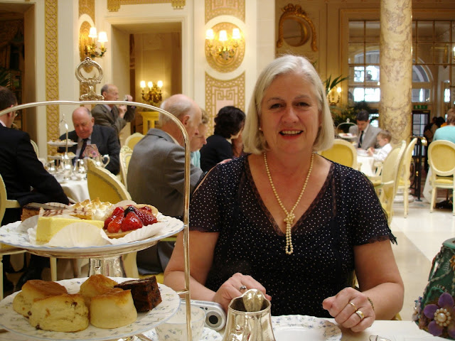 white haired lady, steph's mum, sitting at a table in the Ritz with a big smile and afternoon tea in front of her