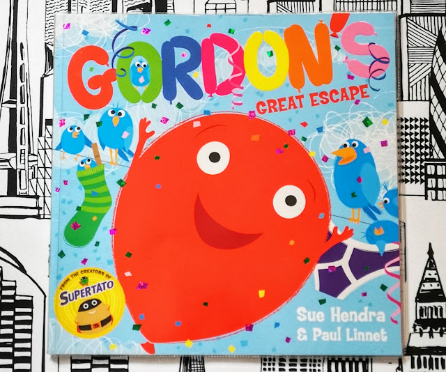 Image of the front cover of the children's book Gordon's Great Escape by Sue Hendra and Paul Linnet. Featuring and illustration of a red balloon with a happy smiling face and various other birds and balloons in the background. There is also an acknowledgement that this book was wirtten by the creators of the Supertato books. The book is placed on a black and white city print backdrop.