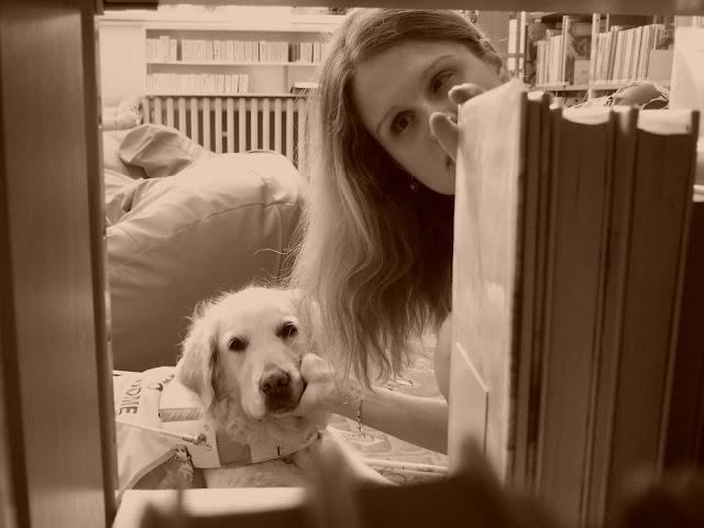 """Linda a Cilka """"vykukují"""" v průhledu regálem s knihami."""