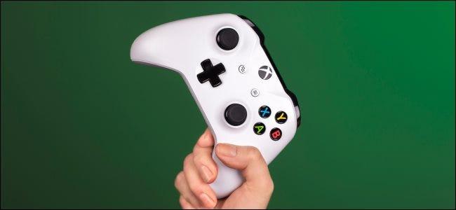 يد تمسك بجهاز تحكم Xbox.