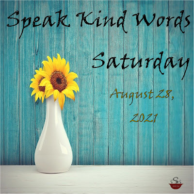 """A white vase with small sunflowers sits on a white table with a teal painted wooden wall behind it. Above the sunflowers it says """"Speak Kind Words Saturday,"""" and to the right August 28, 2021"""