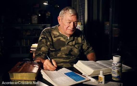Anciano escribe la Biblia a mano