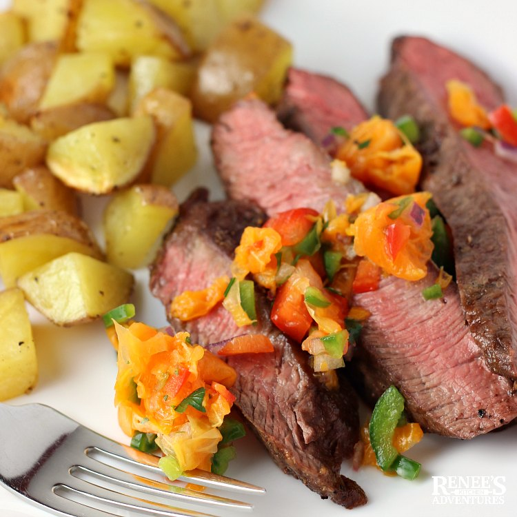 Serving suggestion for Flat Iron Steak with Citrus Salsa by Renee's Kitchen Adventures, sliced flat iron steak with salsa on top, fork, and potatoes on a white plate