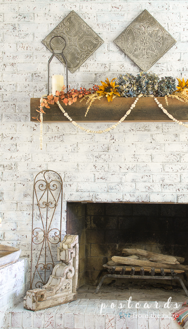 white brick fireplace with muted fall colors and wood corbel and iron fence section