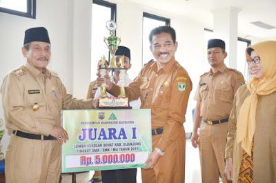 Bupati Yuswir Arifin sedang menyerahkan hadiah kepada kepala sekolah yang meraih juara sekolah sehat