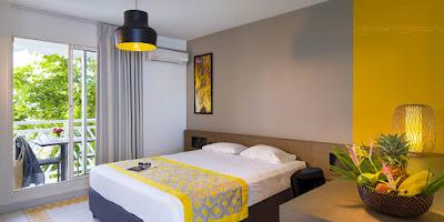 Lit double à l'hôtel Manganao avec vue sur le jardin tropical et corbeille de fruits