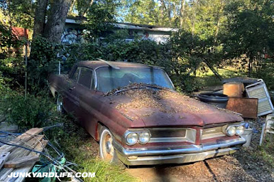 1962 Pontiac Grand Prix sits in yard neglected.