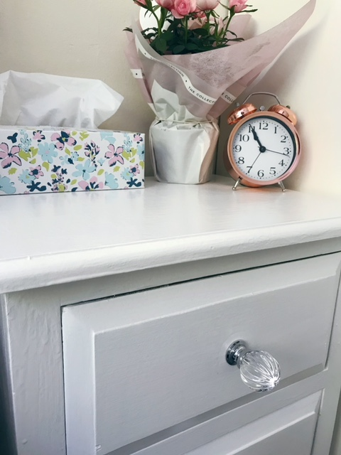 White bedside drawers with a glass knob and a box of tissues, rose plant and alarm clock sitting on top of it