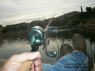 Jimmy's hand holding a fishing rod with boots propped up on tackle box, view of lake beyond feet