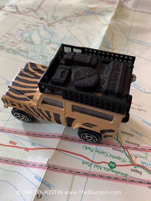 A beige and black painted toy Land Rover on a paper map next to the words BwaBwata National Park.