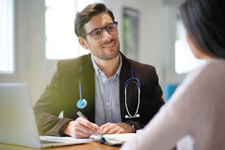 A caucasian male doctor wearing glasses, a jacket and stethoscope around his neck with a laptop open in front of him poised taking notes taking to a patient who has their back to the camera