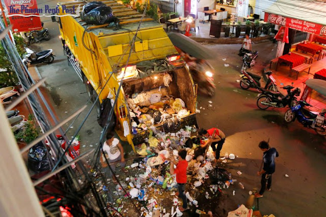 Cintri workers shovel trash into a garbage truck in Phnom Penh last year. Heng Chivoan