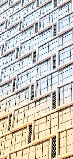 خلفية انعكاس لون الشمس على نوافذ المبنى الزجاجية