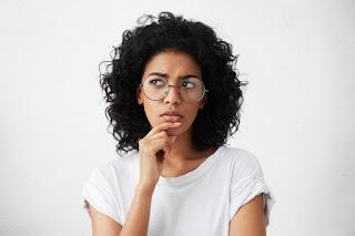 mulher negra de óculos pensativa