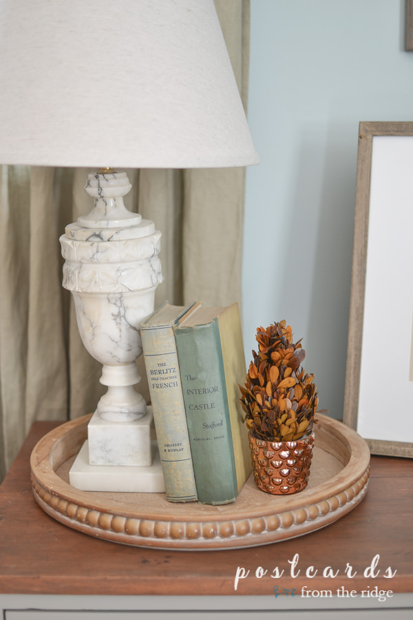 round wooden beaded edge tray with vintage books, vintage marble lamp, fall preserved boxwood topiary