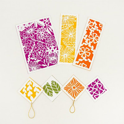 yellow, olive, orange, and dark magenta paper cut gift tags, bookmarks, and art piece